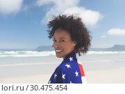 Купить «Woman wrapped american flag at beach», фото № 30475454, снято 14 ноября 2018 г. (c) Wavebreak Media / Фотобанк Лори