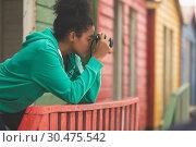 Купить «Woman capturing photograph while standing at beach hut», фото № 30475542, снято 14 ноября 2018 г. (c) Wavebreak Media / Фотобанк Лори