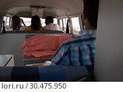 Купить «Man sitting in back of camper van while his friends are sitting in front seats», фото № 30475950, снято 9 января 2019 г. (c) Wavebreak Media / Фотобанк Лори