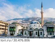 Купить «A minaret rises over buildings across the river from the Old Town neighborhood of Sarajevo. Gazi Husrev-bey Mosque.  Bosnia Herzegovina», фото № 30476806, снято 28 февраля 2018 г. (c) Николай Коржов / Фотобанк Лори