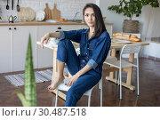Купить «Beautiful woman in denim overalls sits on a chair in the kitchen.», фото № 30487518, снято 18 марта 2019 г. (c) Женя Канашкин / Фотобанк Лори
