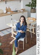 Купить «Beautiful woman sits in the kitchen and uses the phone.», фото № 30487526, снято 18 марта 2019 г. (c) Женя Канашкин / Фотобанк Лори