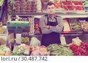 Купить «male seller showing assortment of grocery shop», фото № 30487742, снято 18 марта 2017 г. (c) Яков Филимонов / Фотобанк Лори