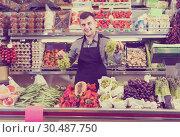 Купить «attentive male seller showing assortment of grocery shop», фото № 30487750, снято 18 марта 2017 г. (c) Яков Филимонов / Фотобанк Лори