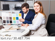 Competent seller in showroom helping young female client to choose furniture materials for her apartment. Стоковое фото, фотограф Яков Филимонов / Фотобанк Лори