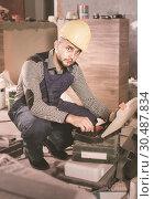 Купить «Builder is choosing tools in suitcase for work», фото № 30487834, снято 3 июня 2017 г. (c) Яков Филимонов / Фотобанк Лори