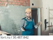 Купить «Builder in the helmet ready is plastering the wall», фото № 30487842, снято 3 июня 2017 г. (c) Яков Филимонов / Фотобанк Лори