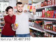 Купить «Clients buying tinned food at grocery store», фото № 30487910, снято 14 марта 2017 г. (c) Яков Филимонов / Фотобанк Лори