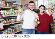 Купить «Ordinary family purchasing tinned food», фото № 30487926, снято 14 марта 2017 г. (c) Яков Филимонов / Фотобанк Лори