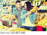Купить «Young couple are deciding on fruits», фото № 30487946, снято 18 марта 2017 г. (c) Яков Филимонов / Фотобанк Лори
