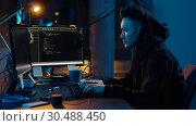 Купить «hacker in hoodie using computers for cyber attack», видеоролик № 30488450, снято 30 марта 2019 г. (c) Syda Productions / Фотобанк Лори