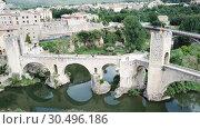 Купить «Aerial view of historic centre of Besalu with Romanesque bridge over Fluvia river, Catalonia, Spain», видеоролик № 30496186, снято 12 июня 2018 г. (c) Яков Филимонов / Фотобанк Лори