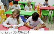 Купить «Cute schoolchildren drawing with teacher in classroom», видеоролик № 30496254, снято 12 декабря 2018 г. (c) Яков Филимонов / Фотобанк Лори