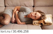Купить «Unhappy woman having stomachache lying on couch at home», видеоролик № 30496258, снято 12 марта 2019 г. (c) Яков Филимонов / Фотобанк Лори