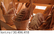 Купить «Breads and baked goods large assortment in decorative baskets on wooden bakery shelves in background slow motion medium shot in 4K», видеоролик № 30496418, снято 5 ноября 2018 г. (c) Uladzimir Sitkouski / Фотобанк Лори