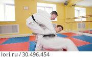 Martial arts. Two athletic men training their aikido skills in the studio. Throwing the opponent on the floor. Стоковое видео, видеограф Константин Шишкин / Фотобанк Лори