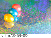 Купить «Easter background. Colored eggs of gold, pink, blue turquoise pearl color on a holographic rainbow background with a copy space», фото № 30499650, снято 31 марта 2019 г. (c) Светлана Евграфова / Фотобанк Лори