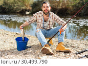 Купить «Lucky fisherman caught a trout fish», фото № 30499790, снято 15 марта 2019 г. (c) Яков Филимонов / Фотобанк Лори