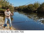 Купить «Adult man standing near river and pulling fish expressing emotions of dedication», фото № 30499798, снято 15 марта 2019 г. (c) Яков Филимонов / Фотобанк Лори