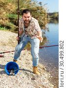 Купить «Adult man standing near river and pulling fish expressing emotions of dedication», фото № 30499802, снято 15 марта 2019 г. (c) Яков Филимонов / Фотобанк Лори