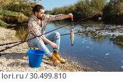 Купить «Positive fisherman holding catch freshwater fish in hands», фото № 30499810, снято 15 марта 2019 г. (c) Яков Филимонов / Фотобанк Лори