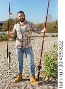 Купить «Happy fisherman with caught fish on a hook and a fishing rod in his hands», фото № 30499822, снято 15 марта 2019 г. (c) Яков Филимонов / Фотобанк Лори