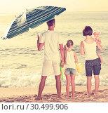 Купить «Young family of four standing with back forward», фото № 30499906, снято 26 июня 2019 г. (c) Яков Филимонов / Фотобанк Лори