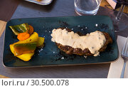 Купить «Prepared veal steak with fried potatoes and pepper sauce served», фото № 30500078, снято 21 апреля 2019 г. (c) Яков Филимонов / Фотобанк Лори