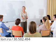 Купить «Students listening to lecture of female teacher», фото № 30502494, снято 29 июня 2020 г. (c) Яков Филимонов / Фотобанк Лори