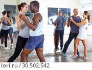 Young positive people dancing together slow ballroom dances in pairs. Стоковое фото, фотограф Яков Филимонов / Фотобанк Лори