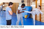Купить «People fighting with coach at gym», фото № 30502554, снято 31 октября 2018 г. (c) Яков Филимонов / Фотобанк Лори