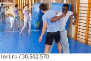 Купить «Two men practicing self defense techniques», фото № 30502570, снято 31 октября 2018 г. (c) Яков Филимонов / Фотобанк Лори