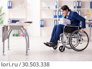 Young male employee in wheelchair working in the office. Стоковое фото, фотограф Elnur / Фотобанк Лори