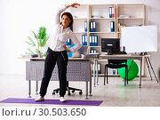 Купить «Middle-aged female employee doing exercises in the office», фото № 30503650, снято 4 декабря 2018 г. (c) Elnur / Фотобанк Лори