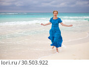 Купить «The woman in a long blue dress goes on the sea coast Cayo Largo island, Cuba», фото № 30503922, снято 1 февраля 2013 г. (c) Куликов Константин / Фотобанк Лори