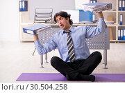 Купить «Young handsome male employee doing exercises in the office», фото № 30504258, снято 6 ноября 2018 г. (c) Elnur / Фотобанк Лори