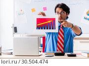 Купить «Young male financial manager working in the office», фото № 30504474, снято 11 октября 2018 г. (c) Elnur / Фотобанк Лори