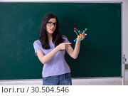 Купить «Young female teacher student in front of green board», фото № 30504546, снято 16 января 2019 г. (c) Elnur / Фотобанк Лори