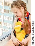 Купить «Russia, Samara, March 2017: A little girl is sitting with a plush dog on the windowsill of a high-rise building. Danger.», фото № 30522658, снято 14 марта 2017 г. (c) Акиньшин Владимир / Фотобанк Лори