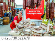 Купить «Russia, Samara, March 2017: a woman salesman with a smile advertises meat sausage products at the fair. Text in Russian: sausages, delicacies, Chernyshova.», фото № 30522678, снято 19 марта 2017 г. (c) Акиньшин Владимир / Фотобанк Лори