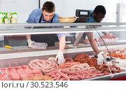 Купить «Skillful butcher with colleague working behind counter», фото № 30523546, снято 20 апреля 2018 г. (c) Яков Филимонов / Фотобанк Лори