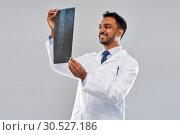 Купить «smiling indian doctor looking at spine x-ray», фото № 30527186, снято 12 января 2019 г. (c) Syda Productions / Фотобанк Лори