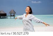 Купить «happy woman over beach and bungalow on background», фото № 30527270, снято 15 июня 2018 г. (c) Syda Productions / Фотобанк Лори