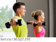 Купить «couple with dumbbells exercising in gym», фото № 30527310, снято 29 июня 2014 г. (c) Syda Productions / Фотобанк Лори