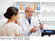 Купить «apothecary with cure and customer at pharmacy», фото № 30527322, снято 27 июня 2015 г. (c) Syda Productions / Фотобанк Лори
