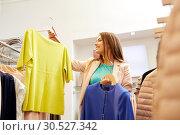 Купить «happy woman choosing clothes at clothing store», фото № 30527342, снято 19 февраля 2016 г. (c) Syda Productions / Фотобанк Лори