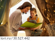 Купить «happy family reading book in kids tent at home», фото № 30527442, снято 27 января 2018 г. (c) Syda Productions / Фотобанк Лори