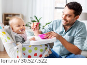 Купить «father feeding happy baby in highchair at home», фото № 30527522, снято 25 августа 2018 г. (c) Syda Productions / Фотобанк Лори