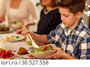 Купить «close up of boy with salad at family dinner party», фото № 30527558, снято 15 декабря 2018 г. (c) Syda Productions / Фотобанк Лори