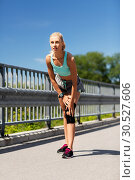 Купить «young woman with knee support brace on leg», фото № 30527606, снято 5 июля 2015 г. (c) Syda Productions / Фотобанк Лори